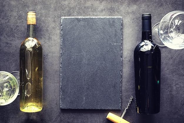 テーブルの上の赤いドライワインのグラス。ダークボトルとグラスワイン。