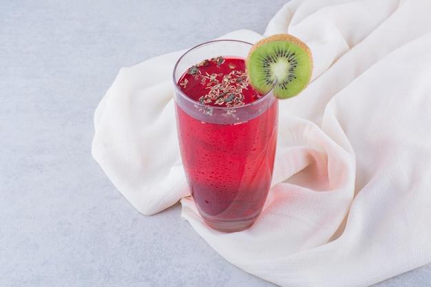 Стакан красного сока на скатерти с ломтиком киви. фото высокого качества