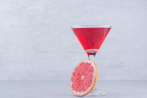 石の背景にグレープフルーツスライスと赤いジュースのガラス。高品質の写真