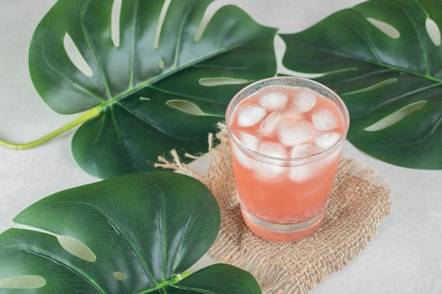 黄麻布に角氷と赤いジュースのガラス