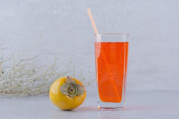 石の背景に柿と赤いジュースのガラス。高品質の写真