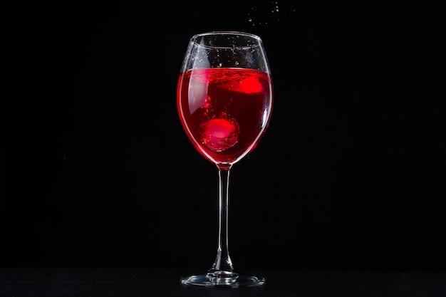 黒の背景に赤いつるのガラス。暗いテーブルの上のワイングラス。カベルネドリンク。