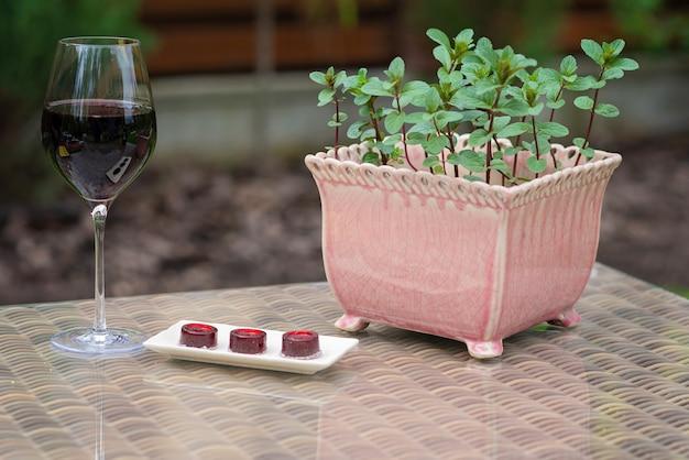 ミントポットの横のテーブルに赤ワインとマーマレードワインキャンディーのガラス。
