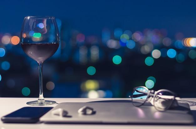 ノートパソコン、スマートフォン、イヤホンをオフにした後、夜に楽しむためにテーブルに置かれた赤ワインのグラス。