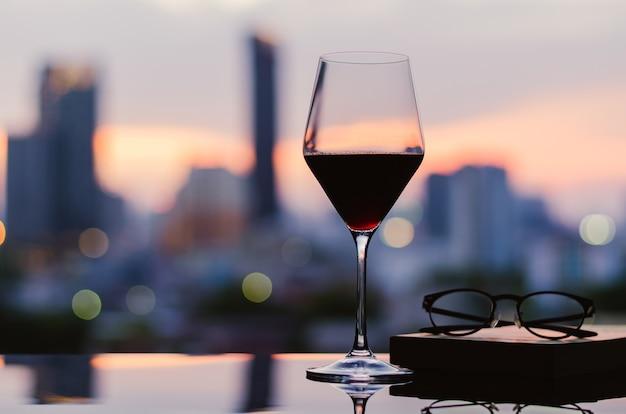 Бокал красного вина с бокалами и книга на столе на фоне города