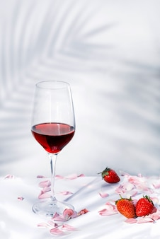 Стакан красного вина с лепестками и немного клубники на белом фоне, с пальмовыми тенями и копией пространства для текста