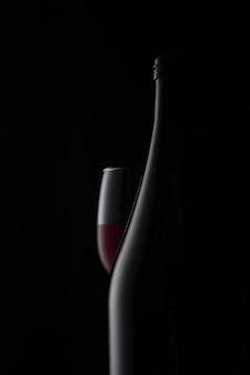 無料で生産するための暗い背景の広告写真にボトルと赤ワインのグラス...