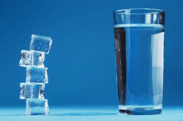 さわやかな水のガラスと青い背景の上の角氷の塔