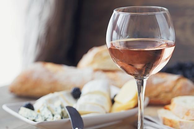 チーズプレート、ブラックベリー、バゲットを添えたロゼワインのグラス。木製の背景にベリーとチーズの品揃え。