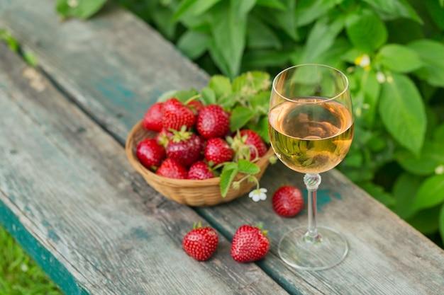木製のテーブルの上に新鮮なイチゴと一緒に出されるロゼワインのグラス