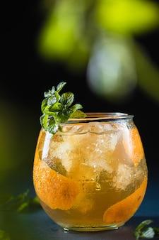 Стакан шотландского виски с апельсиновым соком и украшением свежей мятой