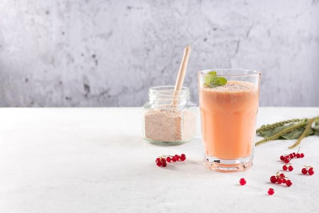 붉은 건포도 열매와 질경이 씨 껍질이 있는 코코넛 밀크로 만든 스무디 한 잔