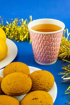 スパークリングウォーター、クリスマスクッキー、青い背景に黄色の見掛け倒しのガラス。クリスマスと新年の装飾。