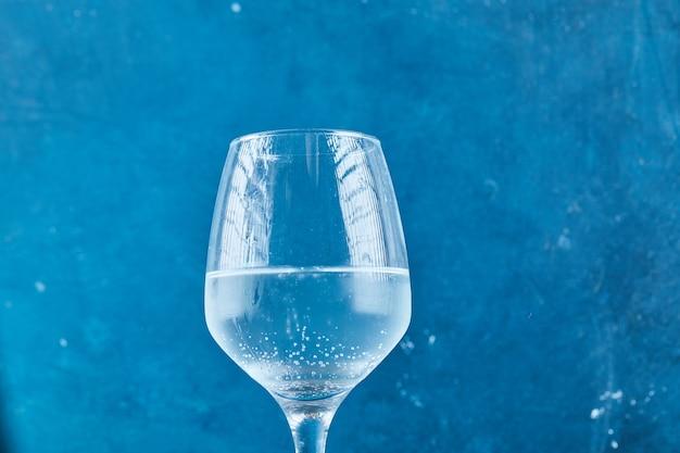 青い表面にスパークリングウォーターのグラス