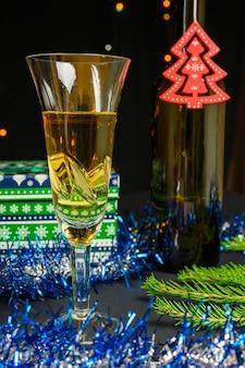 Бокал игристого вина, подарок и елка на бутылке. рождество и новый год концепция на черном фоне.