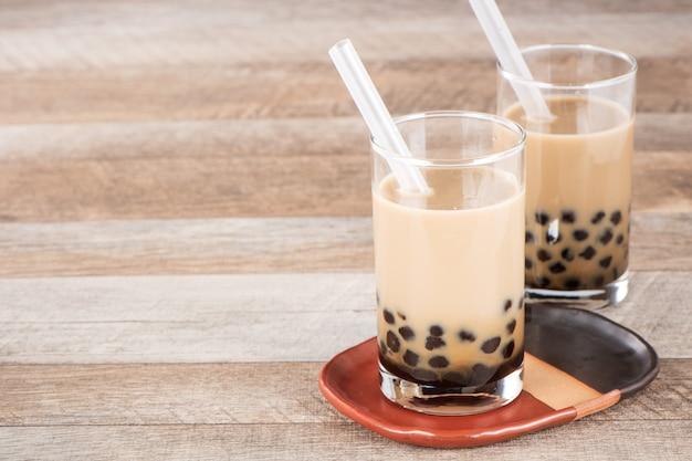 타피오카 진주와 나무 바탕에 짚으로 달콤한 우유 거품 차 한잔. 공간 복사