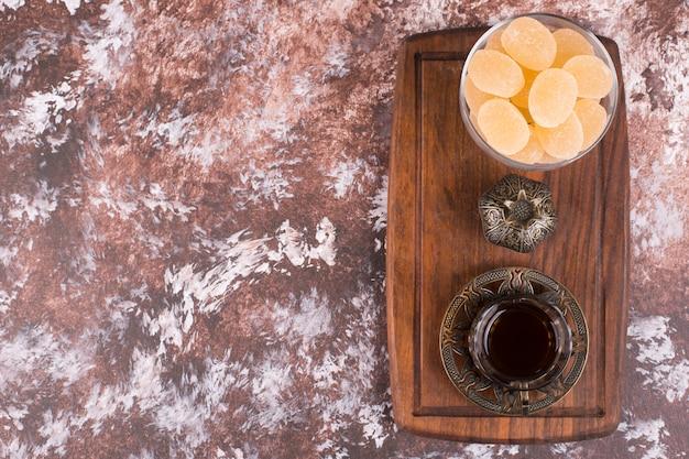 Стакан чая в этнической посуде с мармеладом на деревянном блюде