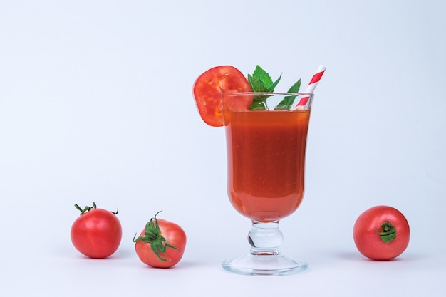 Стакан томатного сока и разбросанных помидоров на белом фоне.
