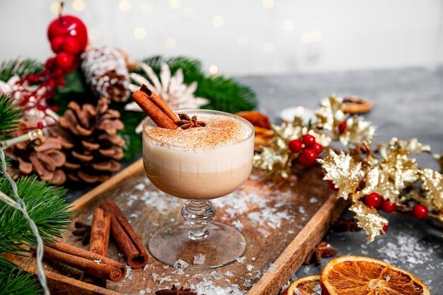 Стакан традиционного рождественского напитка гоголь-моголь на праздничном столе, скопируйте пространство для текста. пряный напиток из яиц и молока с добавлением корицы и кардамона. фото высокого качества