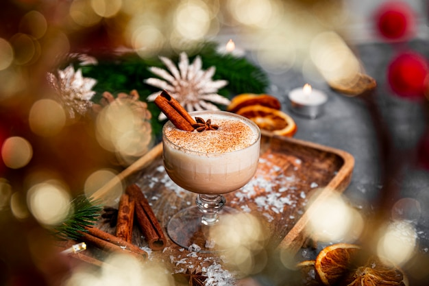 Стакан традиционного рождественского напитка гоголь-моголь на праздничном столе, выборочный фокус. пряный напиток из яиц и молока с добавлением корицы и кардамона. фото высокого качества