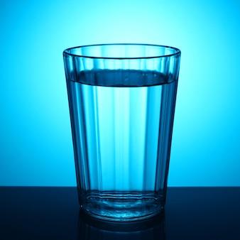 青い背景の上の水のガラス