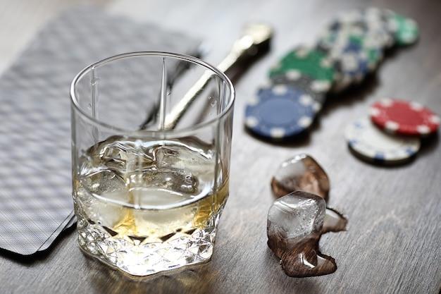 チップとカードとトランプの上のウイスキーと氷のガラス