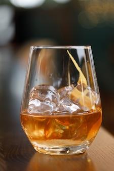 バーの岩の上にウイスキーのグラス。強いアルコールのグラスをクローズアップ-マクロでクローズアップ。