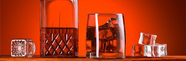 Стакан виски или коньяка, графин и кубики льда, крупный план на деревянном столе. яркий оранжевый коричневый светящийся фон. место для этикеток, текста и логотипа. макет для рекламы.