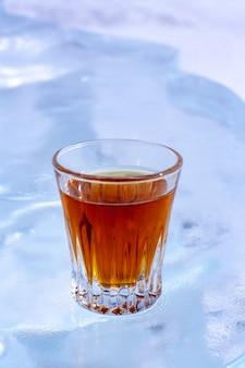 氷の白い背景の上にウイスキーのグラスが立っています。グラスにオレンジ色の飲み物。側面からの上面図。酒類の宣伝に。背景がぼやけています。垂直。