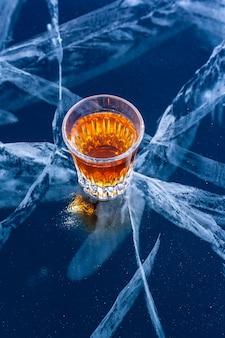 Стакан виски стоит на красивом льду с глубокими трещинами