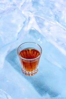 曇らされた氷の上にウイスキーのグラスが立っています。側面からの上面図。アルコール飲料の宣伝用。背景がぼやけています。垂直。