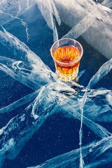 バイカル湖の美しい氷の上にウイスキーが一杯立っています。冷えたウイスキー。美しい深い白い亀裂のある青い氷。側面からの上面図。アルコール飲料の広告。垂直。