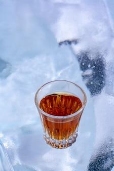 ウイスキーのグラスが白い氷の上に立っています。グラスにオレンジ色の飲み物。側面からの上面図。酒類の宣伝に。背景がぼやけています。垂直。