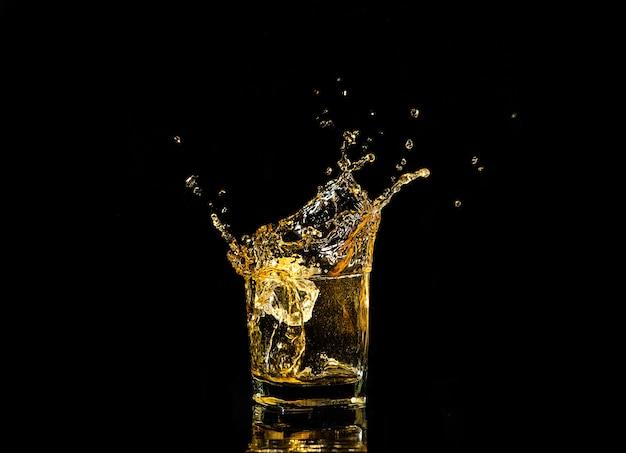 黒の背景上のアイスキューブからの飛散とウイスキーのグラス。