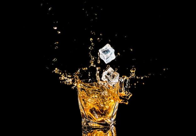 Стакан виски с вкраплениями кубика льда над черным пространством. брызги алкоголя. виски или коньяк или другой сорт алкоголя с вкраплениями.