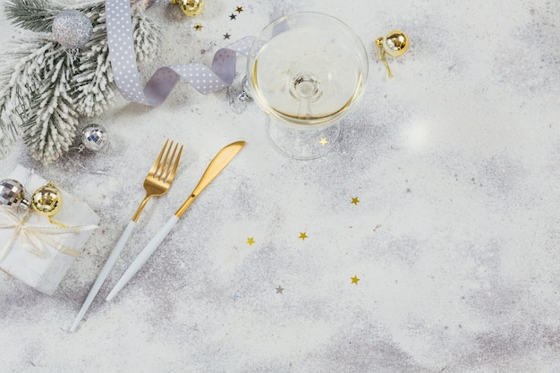 白いスパークリングワインまたはシャンパンのグラスと明るい背景に新年の装飾。冬の休日のコンセプト。テキスト用のコピースペースのある上面図