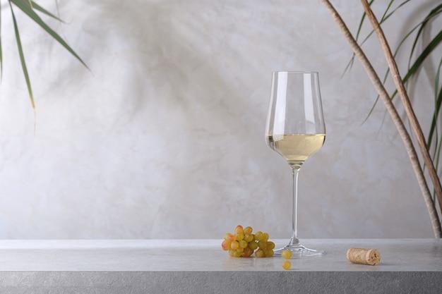 화이트 와인 한 잔, 코르크, 그리고 돌 탁자에 있는 포도 다발. 밝은 배경.
