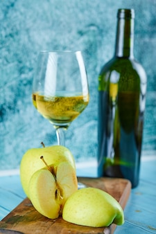 白ワインのグラスと青い壁にリンゴのスライスとボトル。