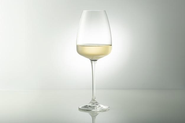 테이블에 화이트 와인 한 잔. 밝은 배경.