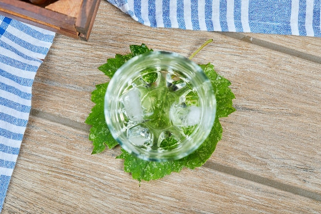 木製のテーブルに氷と白ワインのグラス。高品質の写真
