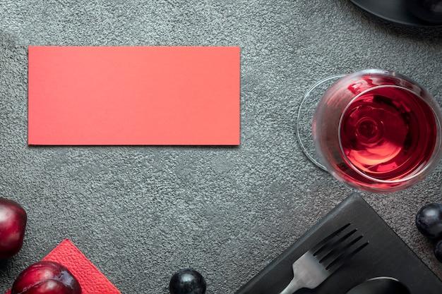 灰色のコンクリートのテーブルにグラスワインと赤いポストカードを置いて、レストランへの招待状を…