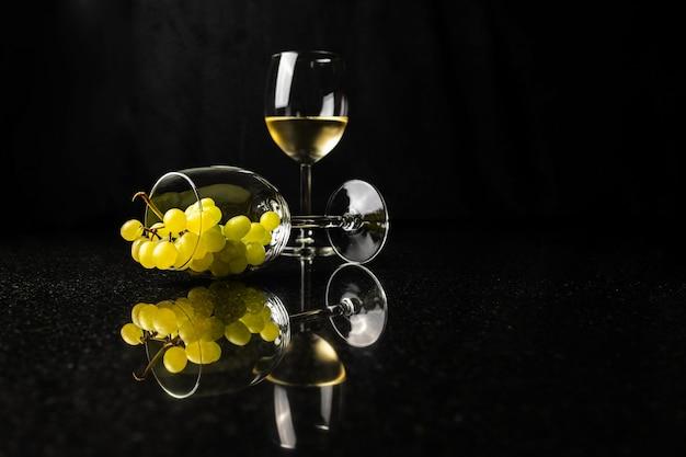 검은 배경에 반사가 있는 포도와 와인 한 잔