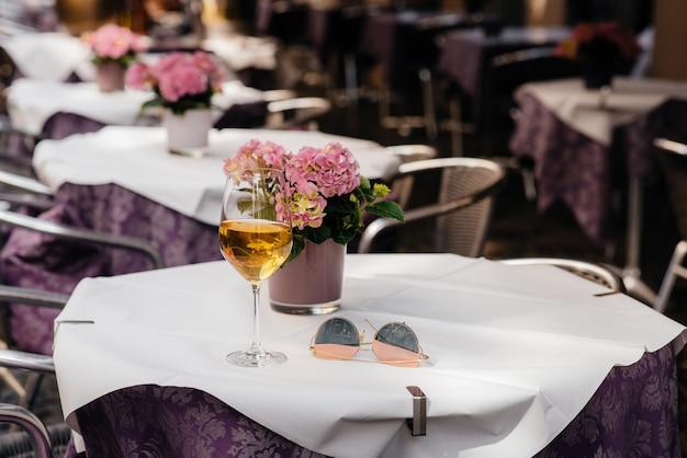 ヨーロッパの中心部にある美しいコーヒーショップのテーブルにワインのグラス。残り