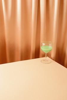 Стакан на углу с зеленым напитком. кремовый занавес на заднем плане. большое пространство для копий для разных целей. простая творческая концепция. модные цвета.