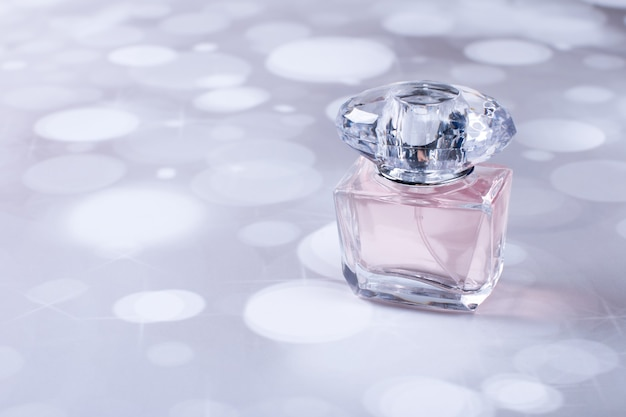 컬러 배경에 유리 향수 병입니다. 향기로운 여성 향수