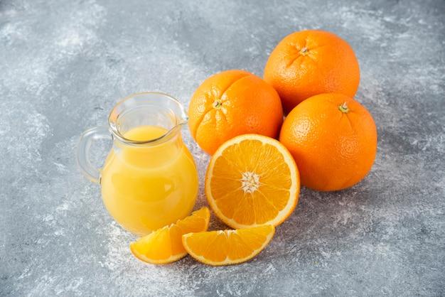 Стеклянный кувшин сока со свежими апельсиновыми фруктами на каменном столе.