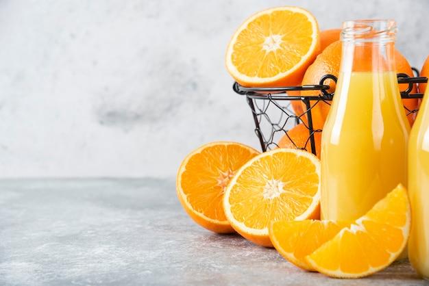 石のテーブルに新鮮なオレンジ色の果物とジュースのガラスピッチャー。