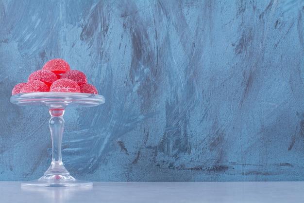 Стеклянная тарелка, полная красных сладких мармеладов на сером столе.