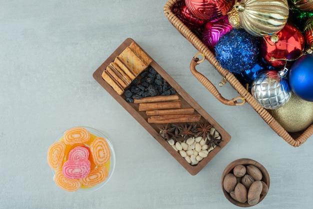 Стеклянная тарелка, полная сахарного мармелада и рождественских праздничных шаров на мраморном фоне. фото высокого качества