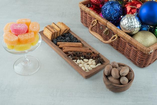 大理石の背景に砂糖マーマレードとクリスマスのお祝いボールでいっぱいのガラス板。高品質の写真